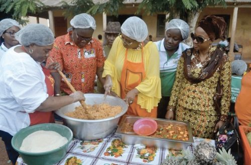 Mrs Cynthia Morrison (3rd left) being assisted by Dr Mrs Gertrude Quashigah (left), the acting National Coordinator of the Ghana School Feeding Programme, to prepare the 'gari fotor. Looking on is Dr Afisah Zakaria (right), the Chief Director of the Gender Ministry