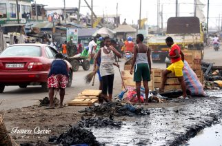 A group of young ladies helping in clearing the filth in the gutter