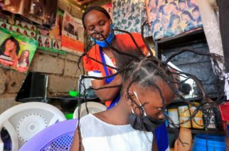 "On Wednesday in Kenya, eight-year-old Stacy Ayuma has her hair threaded. Though the style is not new, some are now playfully calling it ""coronavirus"" because they say it resembles the virus' prickly shape as seen under a microscope. Photo Credit: REUTERS"